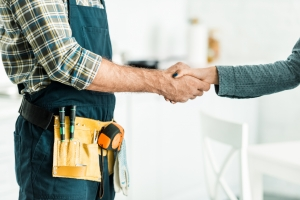 cropped image of plumber and client shaking hands