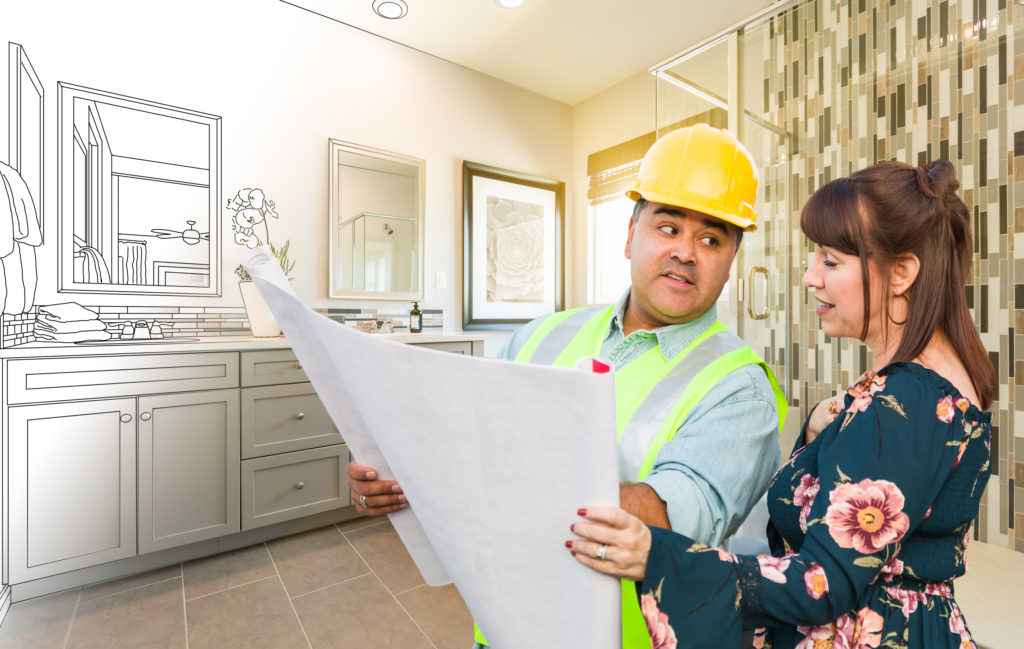 Contractor Talking with Female Client Over Blueprint Plans In Front of Bathroom Drawing Gradating to Photo