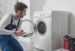 plumber working on washing machine plumbing